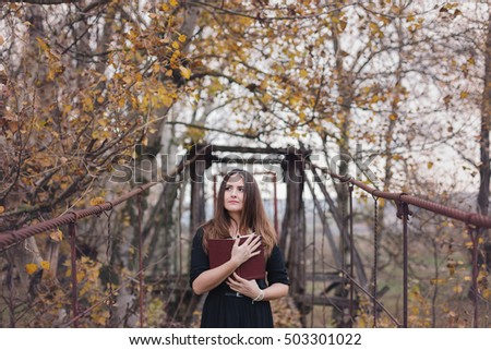 Autumn portrait of a young woman holding a book