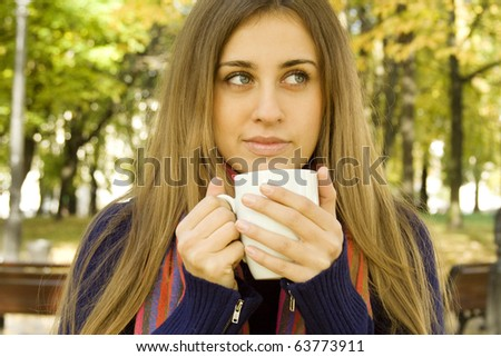Autumn portrait of an attractive young woman wearing a soft sweater and scarf, holding a cup coffee (or tea) - stock photo