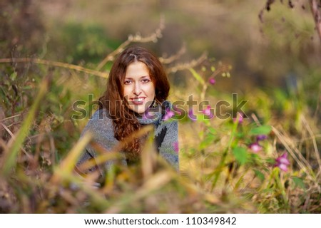 Autumn portrait of happy lovely and beautiful caucasian young woman in field and violet flowers - stock photo