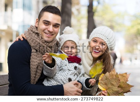 Autumn portrait of happy young cheerful parents with child. Shallow focus   - stock photo