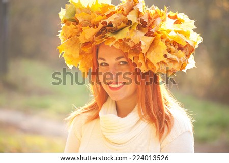 Autumn portrait. Young woman with crown of fall maple leaves