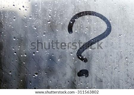 Autumn rain, the inscription on the sweaty glass - question mark - stock photo