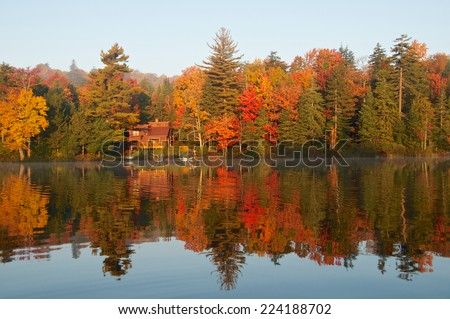 Autumn reflection of trees and cabin highlight the calm lake waters - stock photo