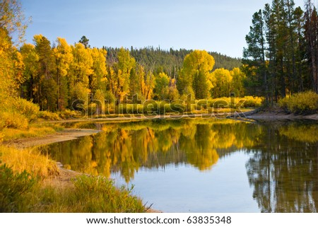 Autumn reflections at a secluded pond in Grand Teton Park - stock photo