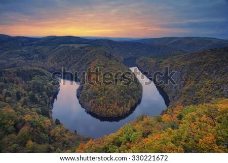 Autumn river bend. Beautiful meander of Vltava river in Czech Republic during autumn sunset. - stock photo