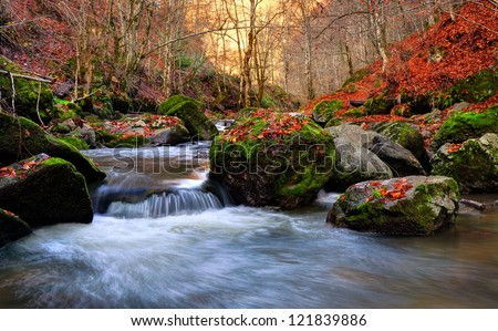 Autumn river cascade with sunlight in background - stock photo