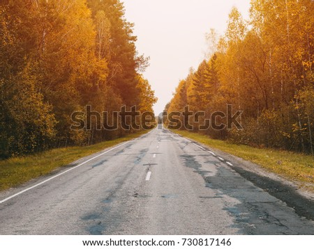 Autumn road car . Terrible pavement on the road in rural areas . Russian roads