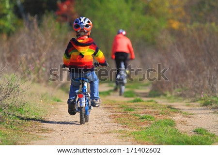 Autumn road with mother and child during leisure ride - stock photo