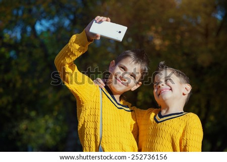 Autumn scene of Happy hugging young brothers taking selfie with a smartphone in the park - stock photo