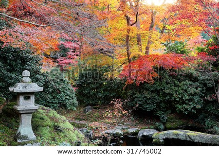 Autumn scenery of a Japanese garden in Kyoto, Japan ~ A stone lantern and fiery maple foliage by the pond in a garden - stock photo