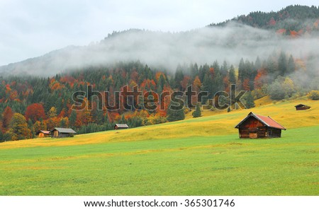 Autumn scenery of Bavarian countryside with grass field and wooden barns in morning fog by the hillside near Garmisch Partenkirchen and Mittenwald, Germany - stock photo