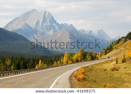Autumn scenic view of rocky mountains, forests and road (highway 40) while traveling in kananaskis country, alberta, canada - stock photo
