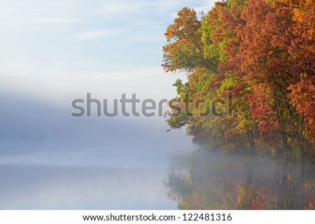Autumn shoreline of Eagle Lake in fog with reflections in calm water, Fort Custer State Park, Michigan, USA - stock photo