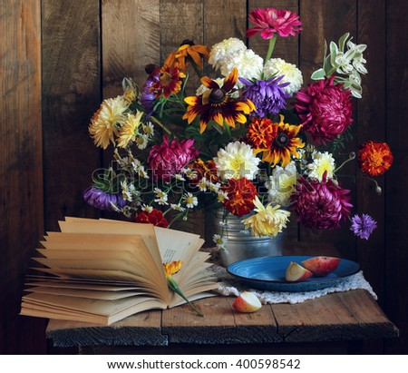 Autumn still life in rustic style with an open book, a bouquet of flowers and pieces of Apple on the blue plate on the background of boards. - stock photo