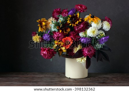 Autumn still life in rustic style with garden flowers in a tin can on a dark background. - stock photo