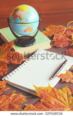 Autumn still life in vintage tones - white checkered notebook with vintage ink pen and old book among the bright yellow maple leaves. Selective focus at the ink pen - shallow depth of field - stock photo