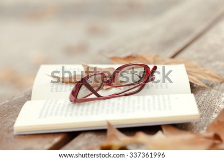 Autumn still life on bench with maple leaves and open book.  - stock photo