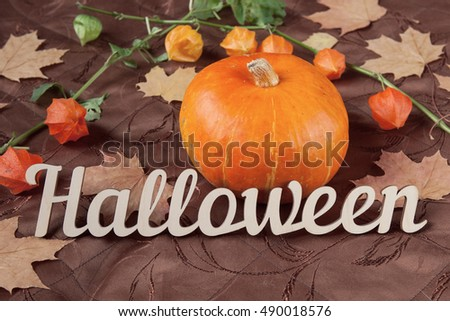 Autumn still life. Pumpkin with flowers, maple leaves and Halloween holiday text