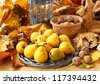 Autumn still life with a lantern-candlestick with pears and nuts on a background abscissed leaves - stock photo