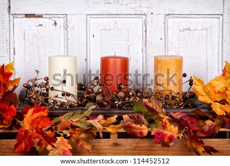 Autumn still life with candles and leaves with an antique wood panel for background - stock photo