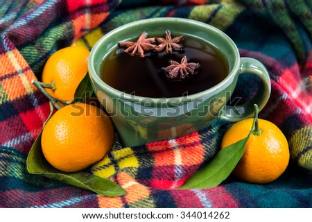 Autumn still life with cup of tea with stars anise, plaid scarf and mandarines with leaves