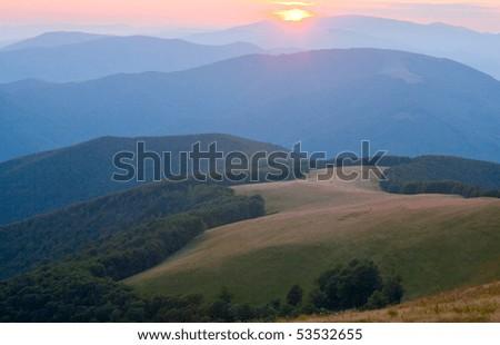 Autumn sunrise mountain view with haze, forest and sun on sky (Carpathian, Ukraine) - stock photo