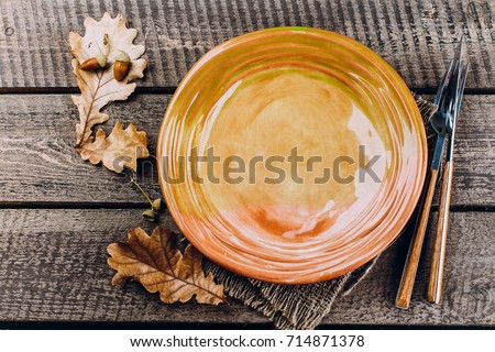 Thanksgiving Dinner Plate With Fork Knife And Leaves On Rustic Wooden