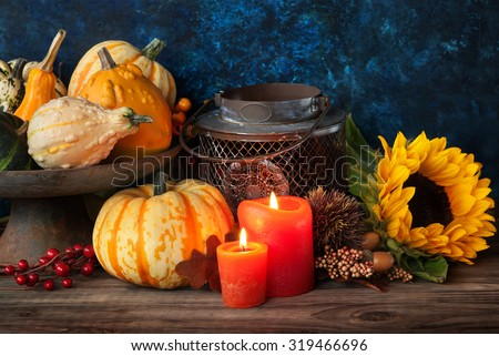 Autumn thanksgiving decor with candle, sunflower and pumpkins - stock photo