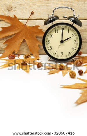 Autumn Time Change / Fall Back / Maple Leaves and an Alarm Clock on a Wooden Background - stock photo