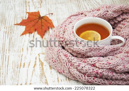 Autumn time: cup of hot tea with lemon and scarf - stock photo