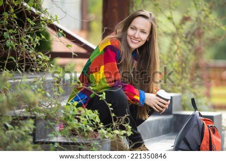 Autumn traveler woman enjoy her walking trip relaxing drinking hot tea in road cafe - stock photo