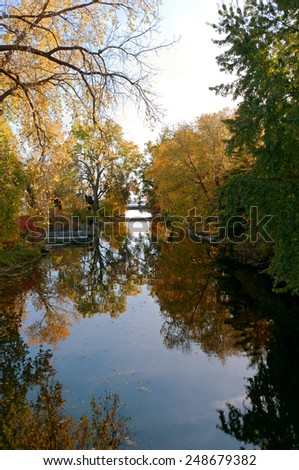 autumn trees reflected in starkweather creek and bridge crossing in olbrich botanical gardens of madison wisconsin - stock photo