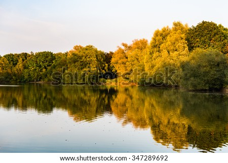 Autumn trees with golden and green leaves reflected in pond.  Beautiful outdoor nature scenery in fall, forest and river with water reflections - stock photo