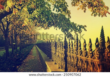 Autumn vintage seafront with fence and dry leaves - stock photo
