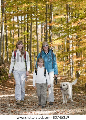 Autumn walking in forest - family with dog on trek (copy space) - stock photo