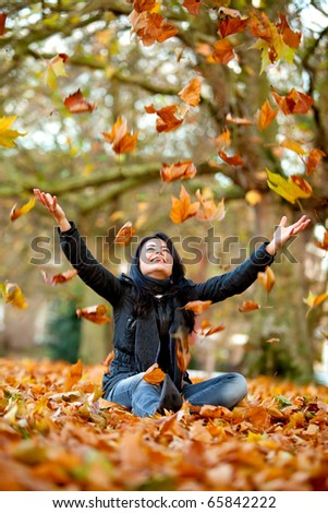 Autumn woman at the park throwing leaves in the air - stock photo