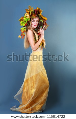Autumn Woman. Beautiful makeup. Golden dress. Dark blue gray background - stock photo