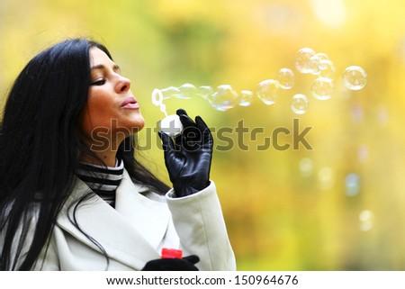 autumn woman blow bubbles portrait in park - stock photo