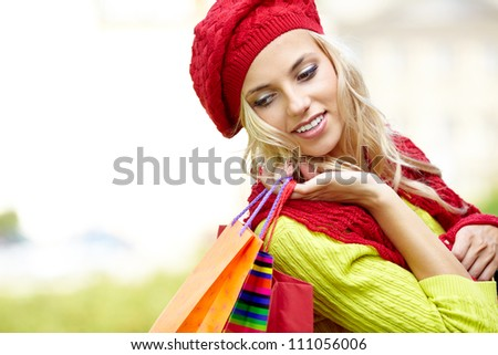 Autumn woman carrying shopping bags walking city street