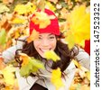 Autumn woman happy with colorful fall leaves falling in forest foliage. Excited cheerful girl looking at camera joyful with beautiful autumn colors. Multiracial Asian Caucasian female model outside. - stock photo