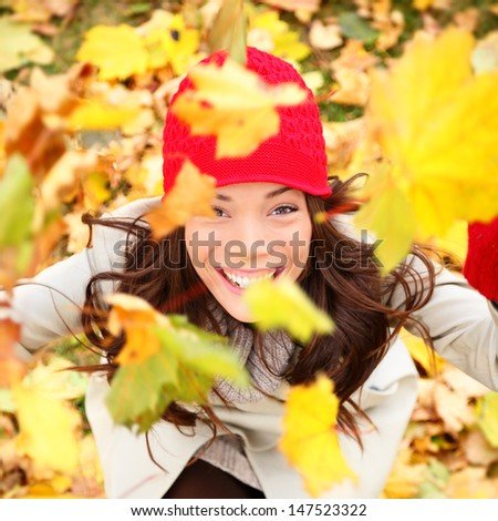 Autumn woman happy with colorful fall leaves falling in forest foliage. Excited cheerful girl looking at camera joyful with beautiful autumn colors. Multiracial Asian Caucasian female model outside.