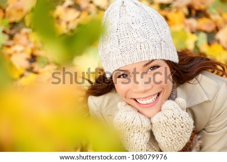 Autumn woman in yellow leaves portrait. utumn portrait of happy lovely and beautiful mixed race Asian Caucasian young woman in forest in fall colors. - stock photo