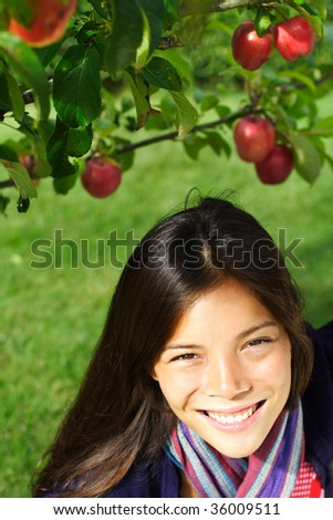 Autumn woman under apple tree - stock photo