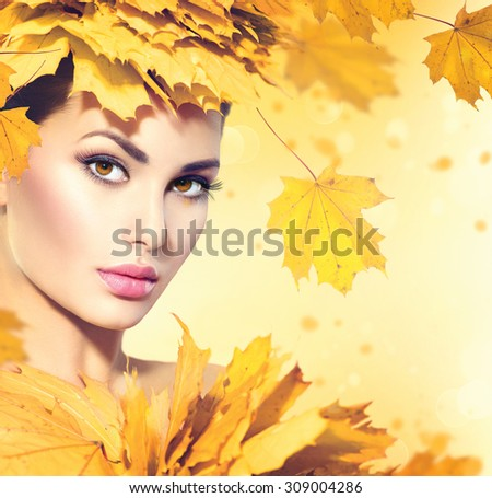 Autumn woman with yellow leaves hair style. Autumn Lady Portrait. Beauty Fashion Art Model Girl with Autumnal Make up and Hairstyle. Fall. Creative Autumn Makeup. Beautiful Face - stock photo
