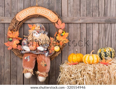 Autumn wreath hanging on a wood background with gourds on a straw bale - stock photo