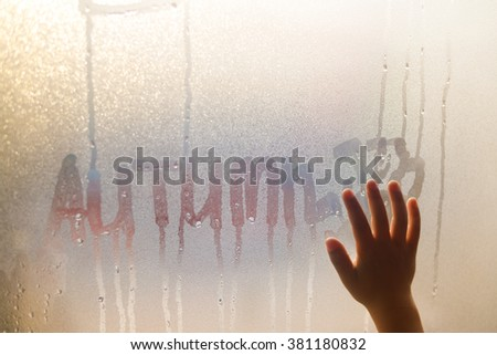 Autumn written and child hand on fogged window, close up sign. Drops of rain on glass background - stock photo