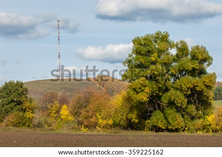 autumn yellow trees foothills. telephone relay tower - stock photo