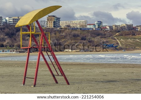 Autumnal gloomy sea scenery with old abandoned weathered lifeguard tower on a deserted beach, Black Sea shore, Constanta, Romania. - stock photo