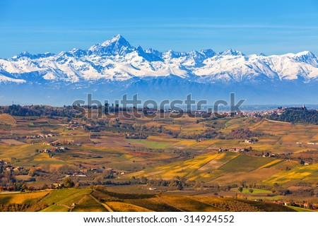 Autumnal hills and snowy mountain ridge on background in Piedmont, Northern Italy. - stock photo