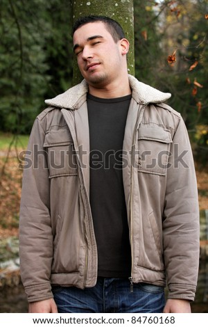 Autumnal portrait of a young man leaning on a tree. - stock photo
